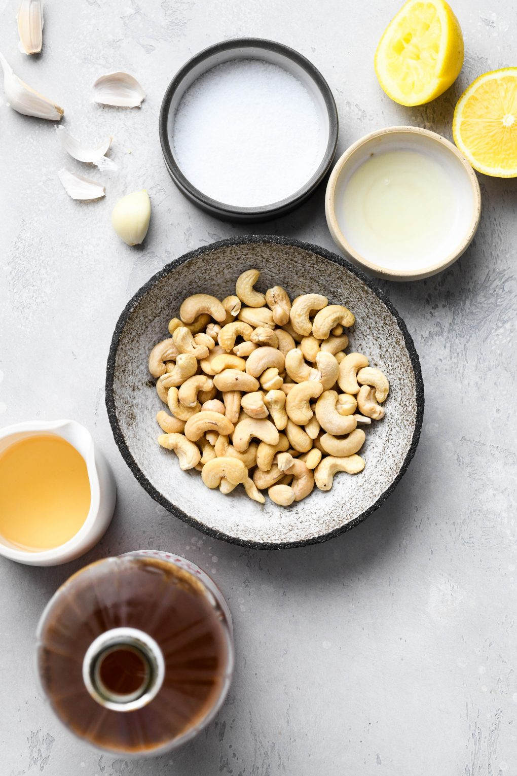 Overhead shot of the ingredients for vegan sour cream - raw cashews in a small rustic looking grey browl, apple cider vinegar, lemon juice, salt, a peeled garlic clove, and some cut lemon wedges. On a light grey textured background.