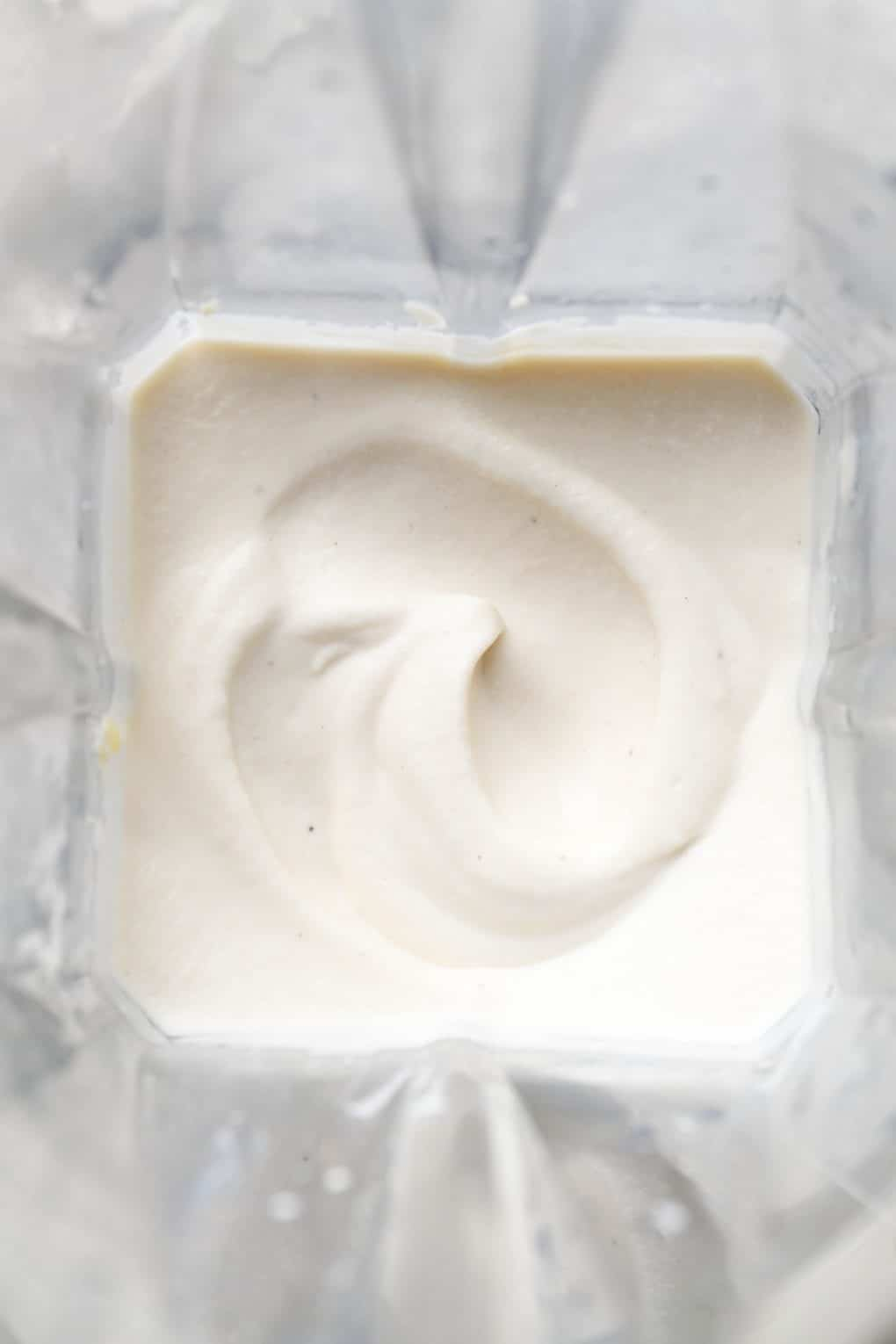 Image of swoopy smooth blended vegan sour cream inside a blender container.