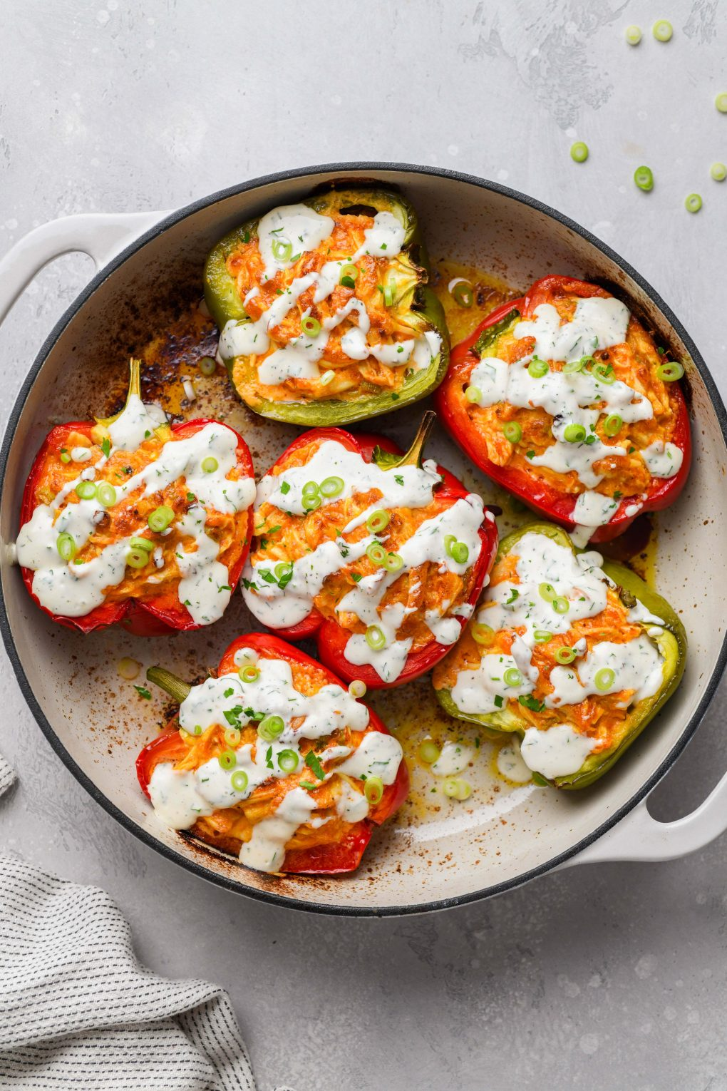 Overhead shot of colorful buffalo chicken stuffed bell peppers in an enameled cast iron skillet. Drizzled with dairy free ranch and topped with fresh herbs and thinly sliced green onion.