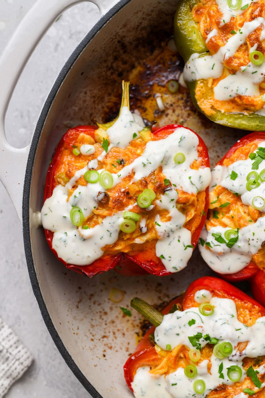 Overhead shot of colorful buffalo chicken stuffed bell peppers in an enameled cast iron skillet. Drizzled with dairy free ranch and topped with fresh herbs and thinly sliced green onion. On a light grey background next to a white and navy striped linen.