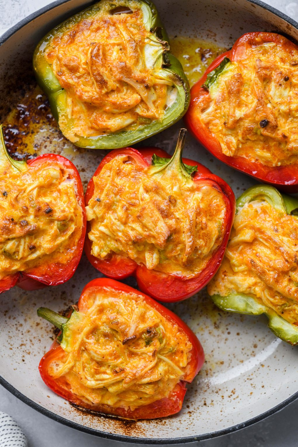 Baked bell peppers filled with shredded buffalo chicken mixture in an enameled white skillet.