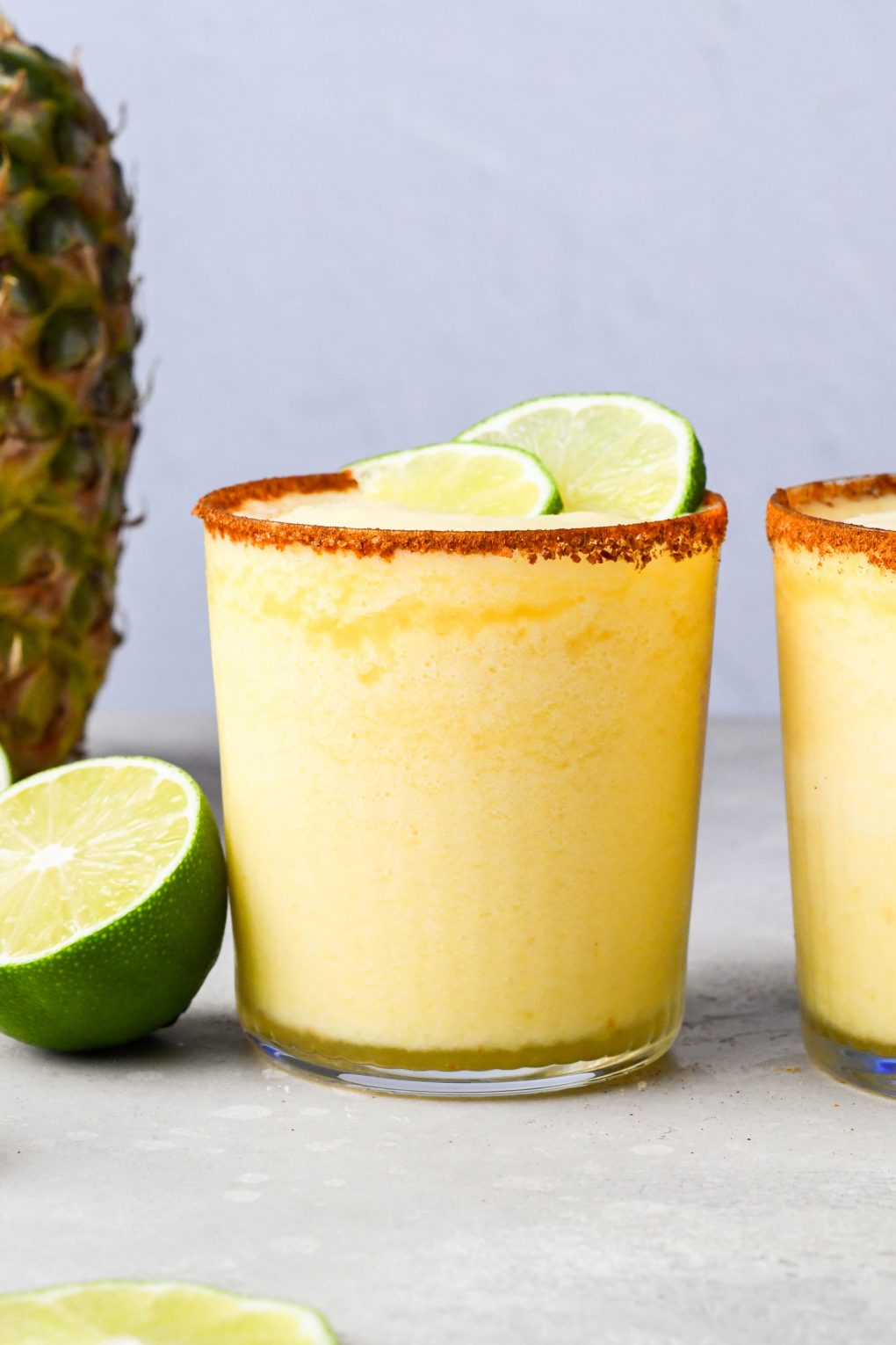 Close up shot of two frozen pineapple margaritas lined with a chili lime salt rimmed glasses. Next to a cut lime and fresh pineapple.