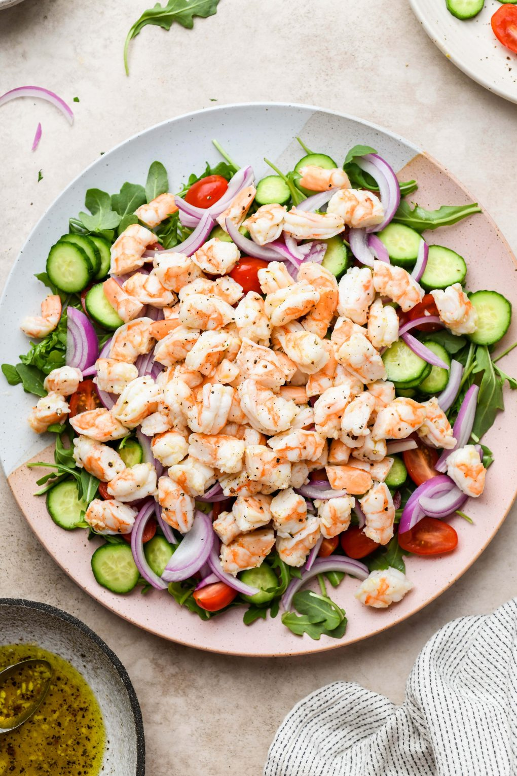 Image of large platter with arugula, cut cucumber, tomatoes, avocado, thinly sliced red onion, and marinated shrimp. On a light beige background.