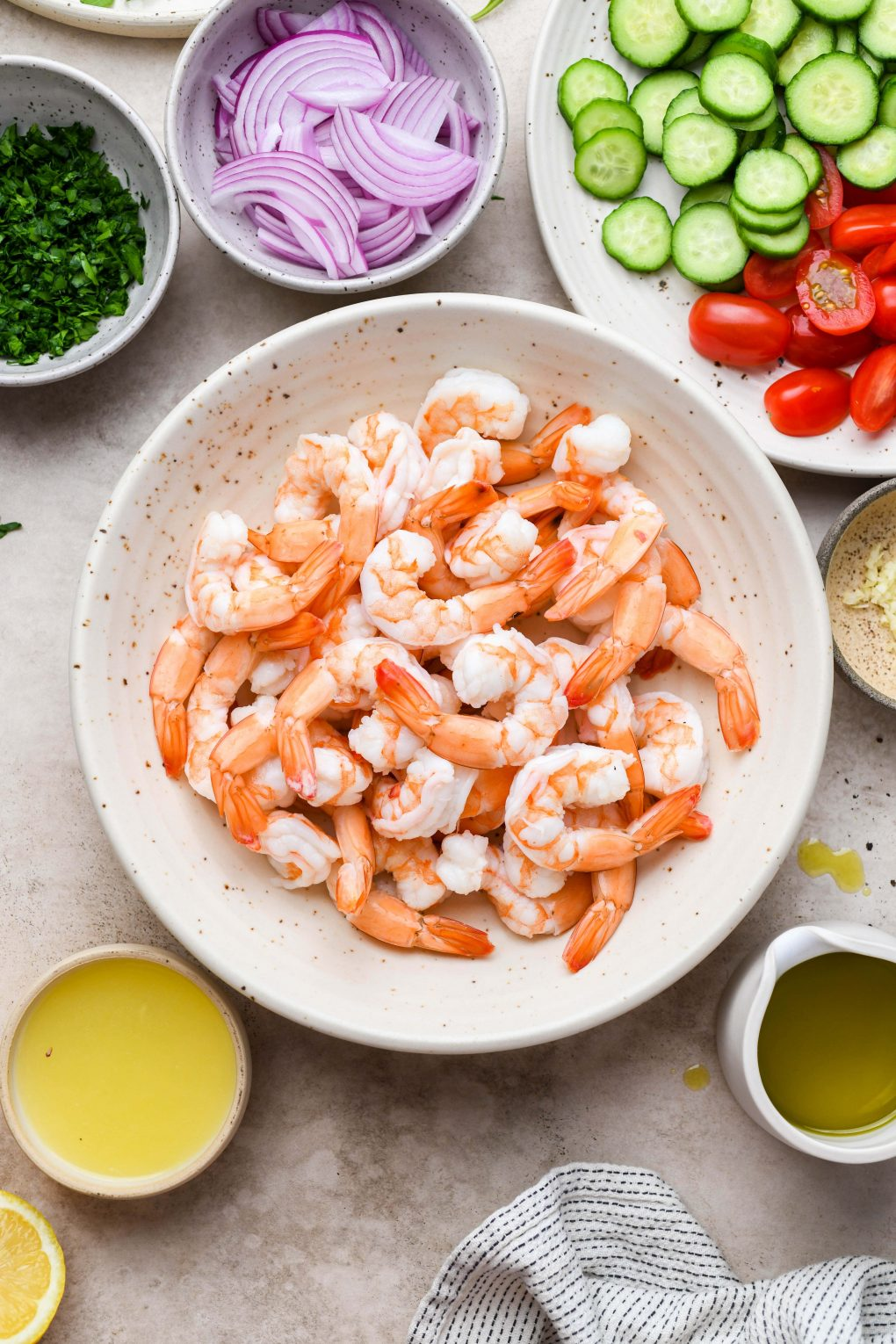 Image of a large speckled bowl filled with pre-cooked shrimp, on a light beige background next to various bowls of other salad ingredients.