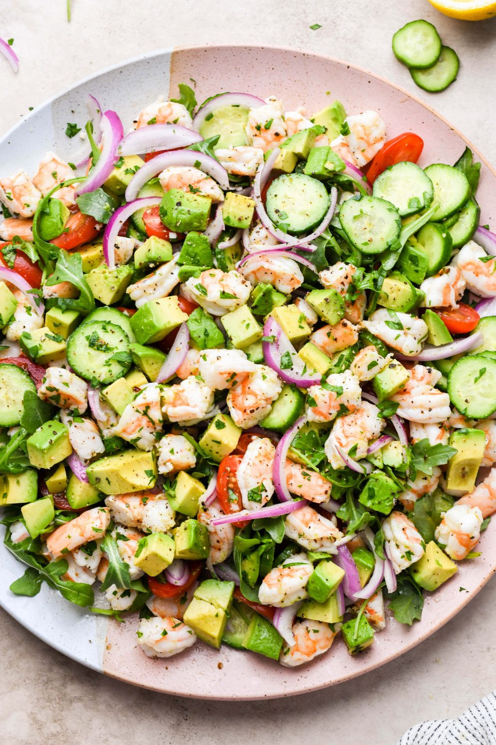 Overhead shot of a fresh and colorful shrimp and avocado salad on a pale pink and beige platter. Salad is made of arugula, sliced cucumber, cherry tomatoes, thinly sliced red onion, avocado, chopped shrimp, and fresh parsley.