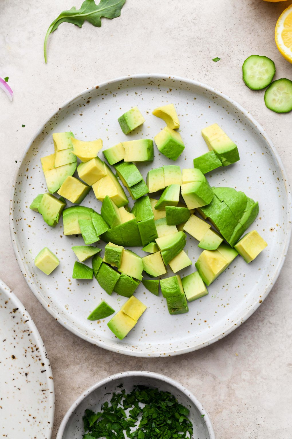 A medium sized speckled plate filled with chopped avocado. On a light beige background.