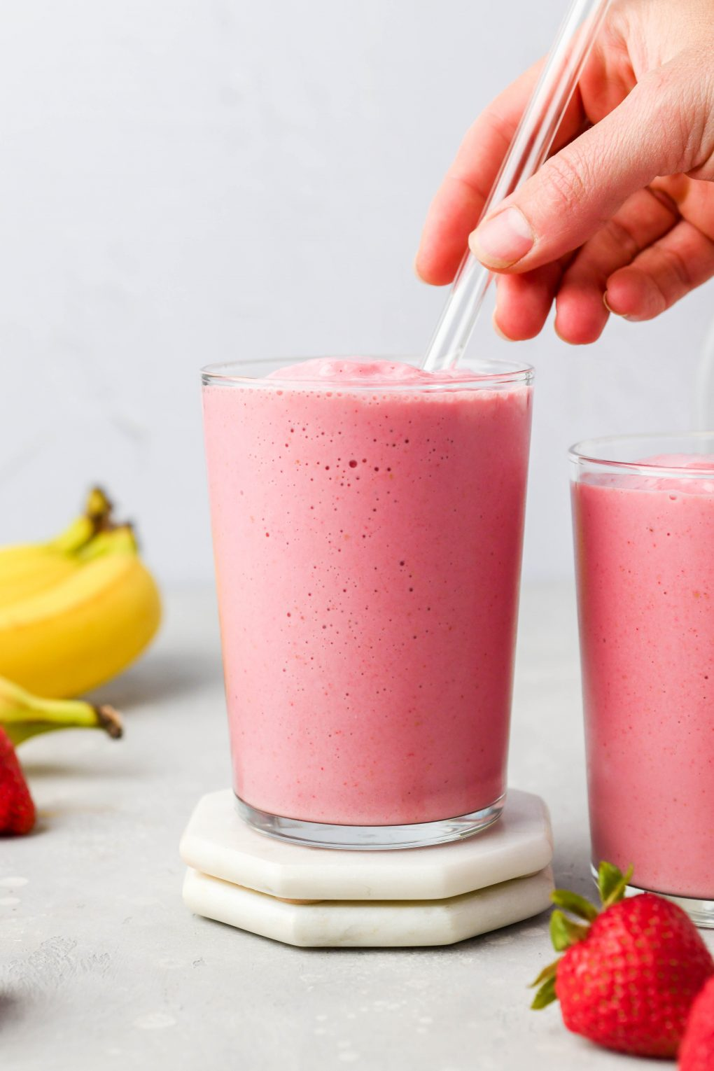 A hand reaching into the frame to place a glass straw into a glass filled with strawberry banana smoothie. On a light colored background next to some fresh strawberries and a small bunch of bananas.