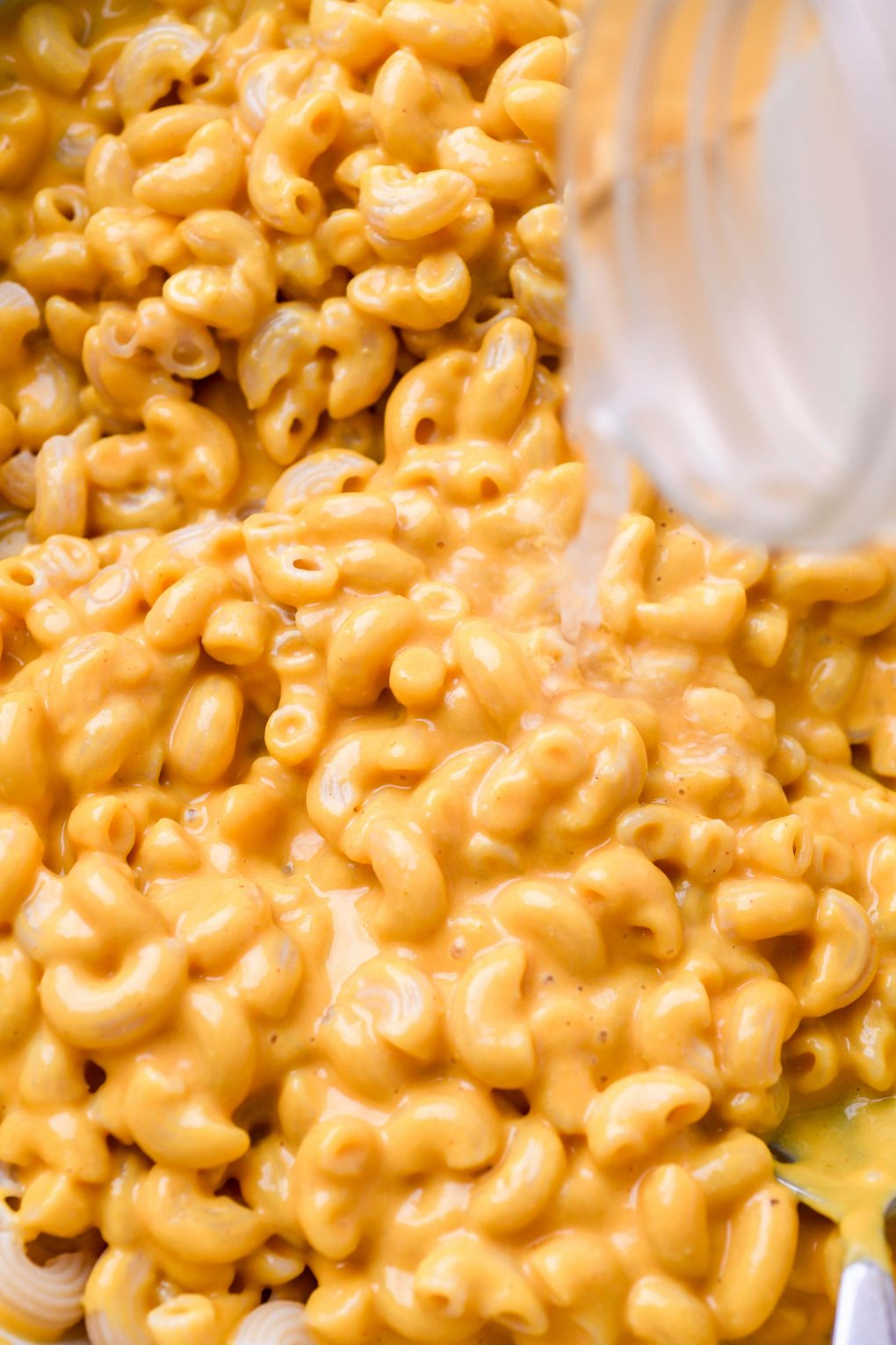 Super close up shot of a glass jar pouring some reserved pasta water into creamy vegan mac and cheese
