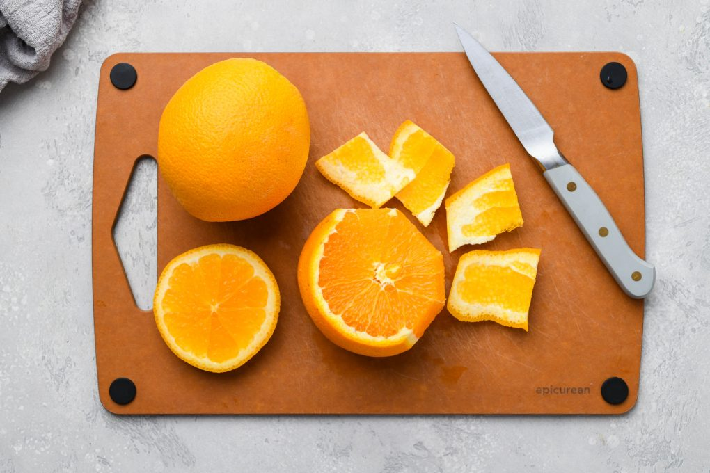 Image of a cutting board with 2 oranges. One is whole and the other is cut open, and the peel is being cut away with a small paring knife.