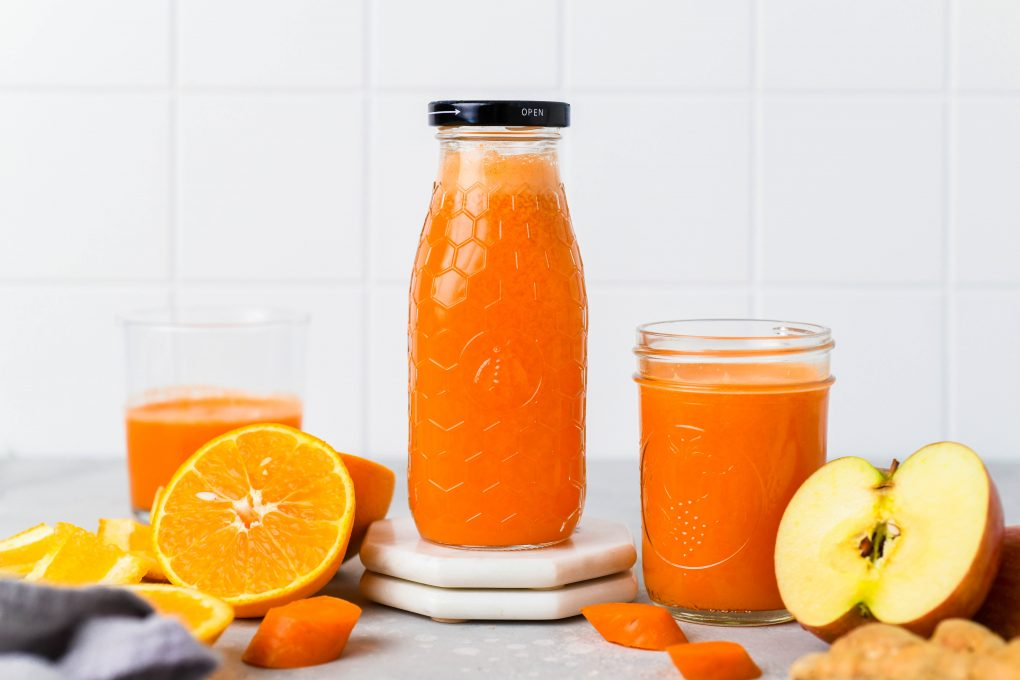 Straight on shot of a textured glass jar filled to the brim with bright orange carrot, apple, and orange juice with ginger. Next to some cut oranges, carrot pieces, and other glass jars of juice - on a light colored background.