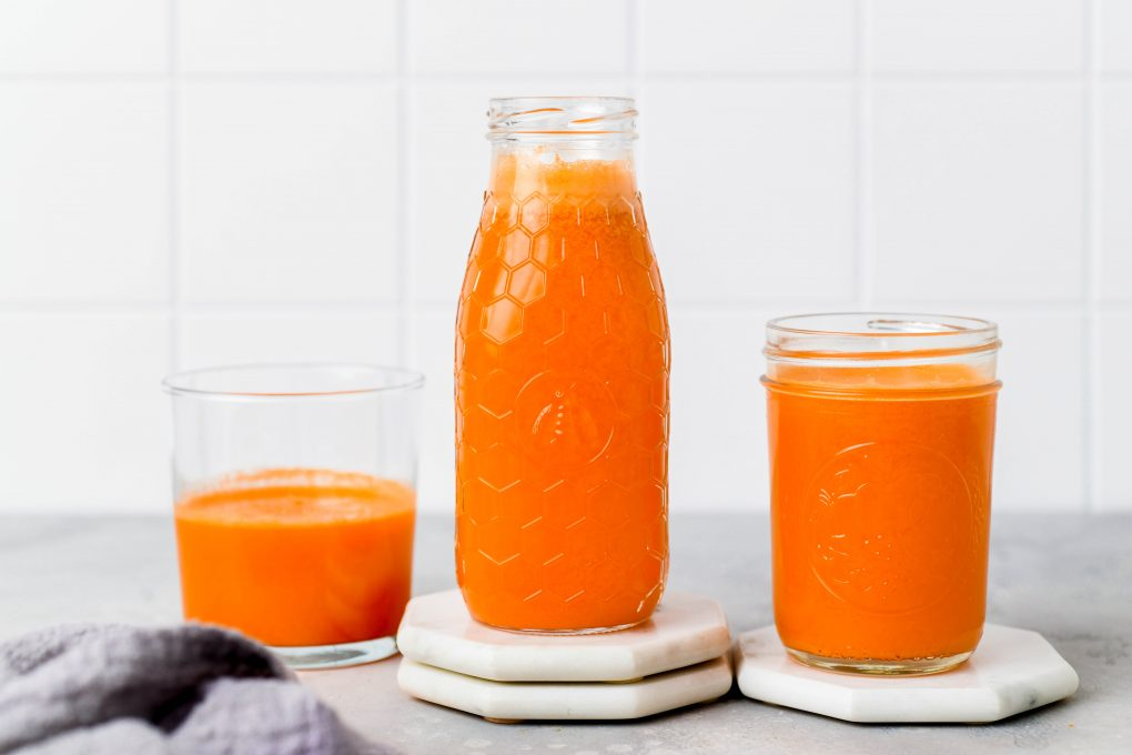 Straight on shot of a textured glass jar filled to the brim with bright orange carrot, apple, and orange juice with ginger. Next to some other small glasses of juice on a light colored background.