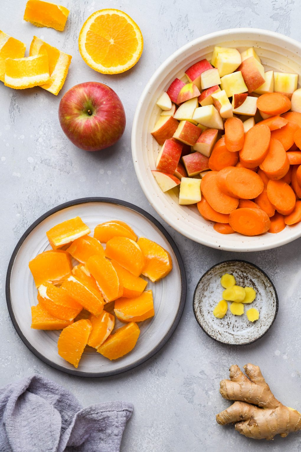 Overhead image for the ingredients used to make carrot, apple, orange juice with ginger. On a light colored background.