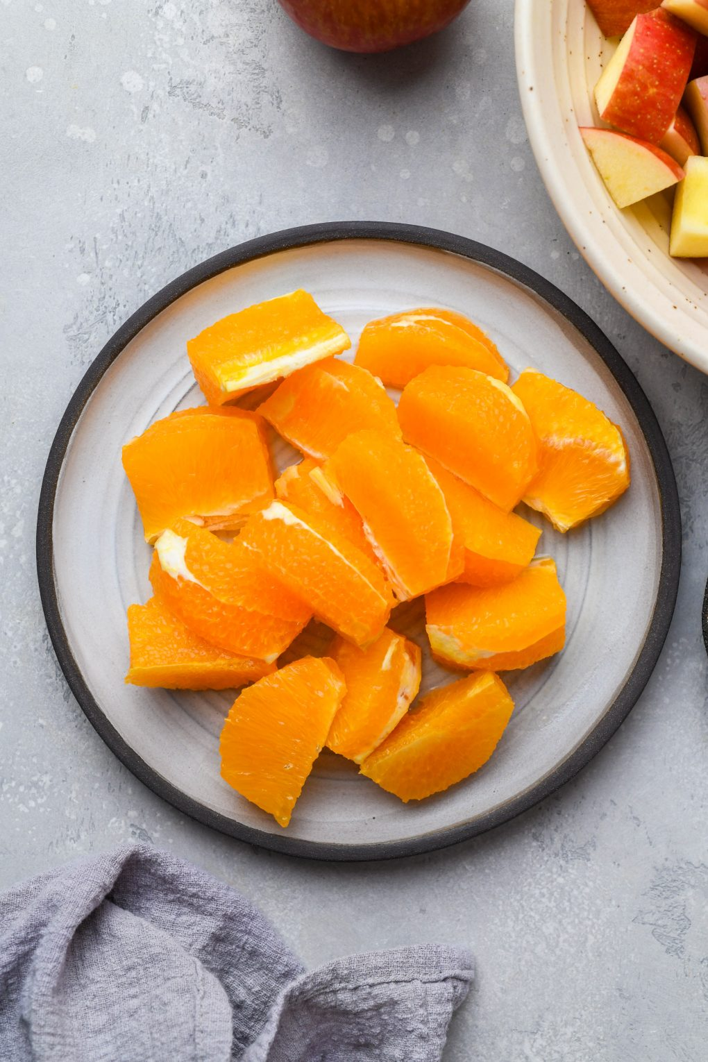 A plate of orange segments on a light colored background.
