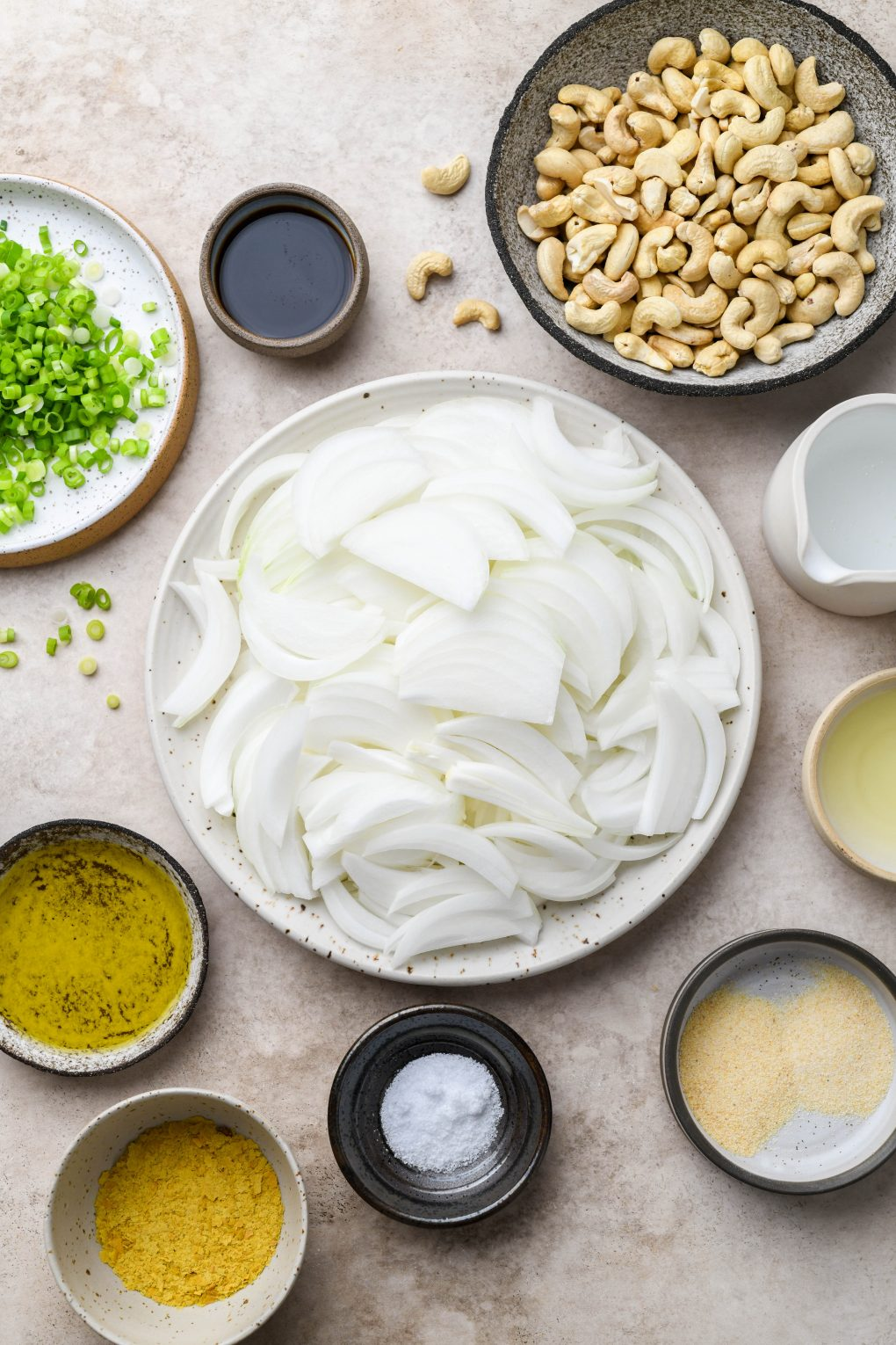Image of all the ingredients needed to make dairy free french onion dip - thinly sliced onion, raw cashews, green onion, spices, water, lemon juice, and coconut aminos. On a light brown background.