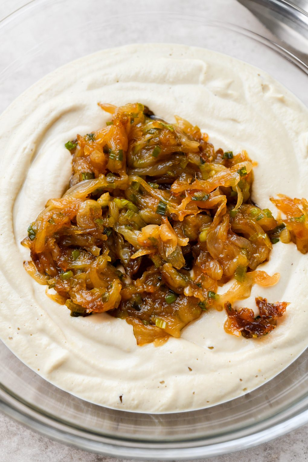 Image of a glass bowl of cashew cream base for french onion dip, topped with a large portion of caramelized onions.