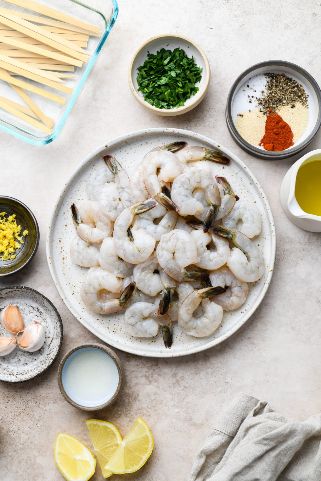 All of the ingredients for garlicky grilled shrimp skewers. Raw tail on shrimp, spices, parsley, olive oil, garlic, lemon zest, and lemon juice. On a light colored background.