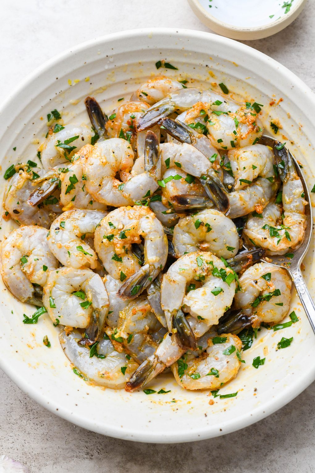 Overhead shot of a large shallow bowl with raw tail on shrimp, tossed together with all the ingredients for the zesty marinade - parsley, spices, lemon zest, lemon juice, and garlic.