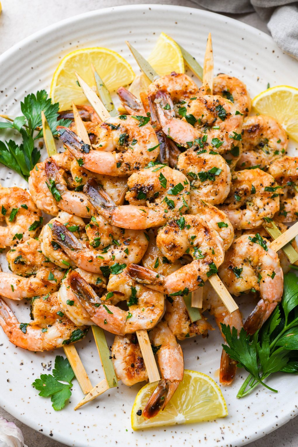 Overhead image of grilled shrimp on wooden skewers. On a light colored speckled plate topped with chopped parsley and next to some lemon wedges.