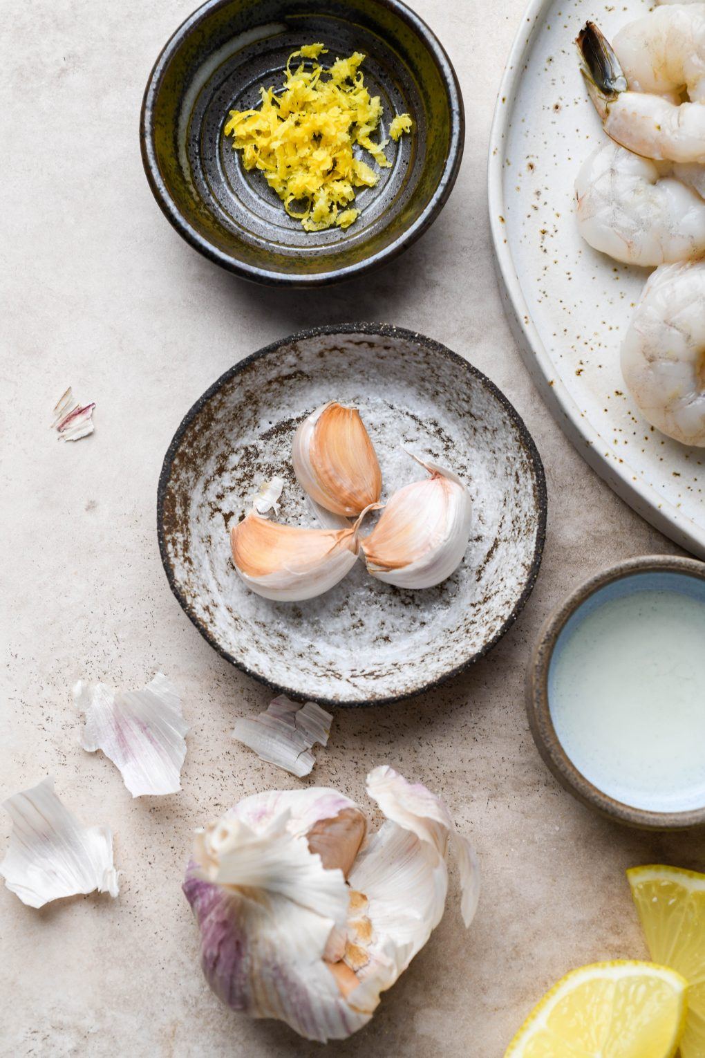A small textured dish filled with 3 garlic cloves. Surrounded by some scattered garlic skin, a dish of lemon zest, and a small bowl of lemon juice. On a light colored background.