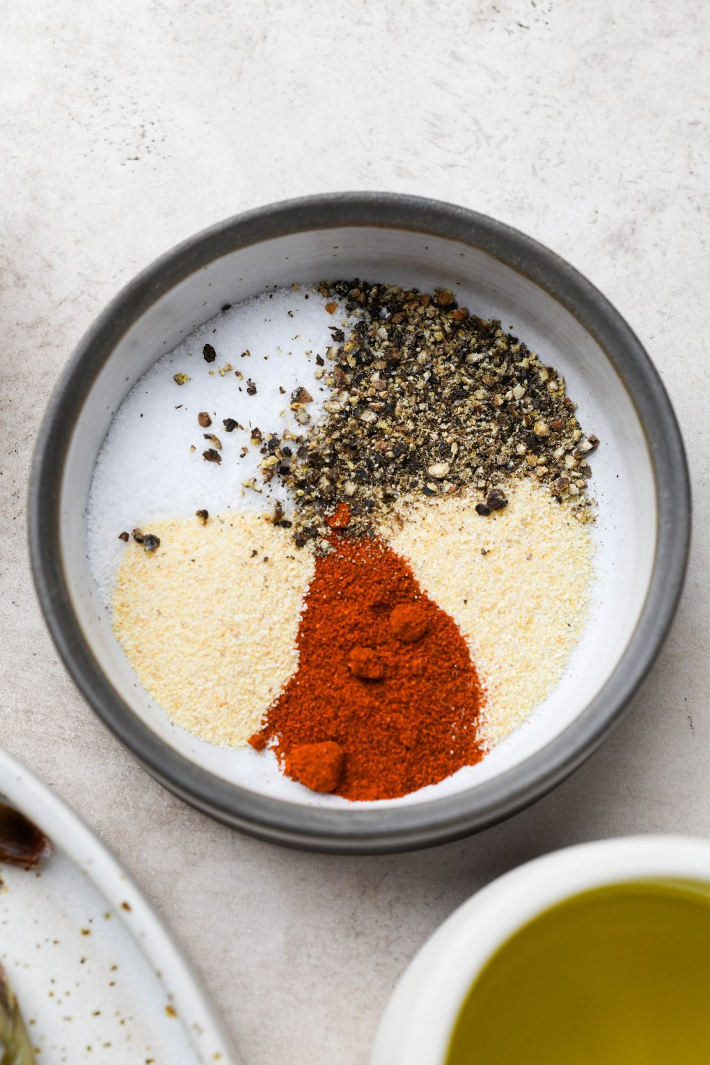Small shallow bowl filled with a spice blend of paprika, garlic powder, onion powder, salt, and pepper. On a light colored background.