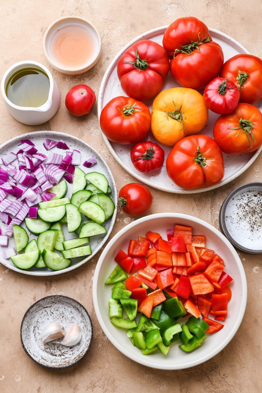 Overhead view of all the ingredients for healthy gazpacho. A large plate of heirloom tomatoes, chopped bell peppers, diced red onion, sliced cucumber, garlic, olive oil, sherry vinegar, salt and pepper. On a light brown background.