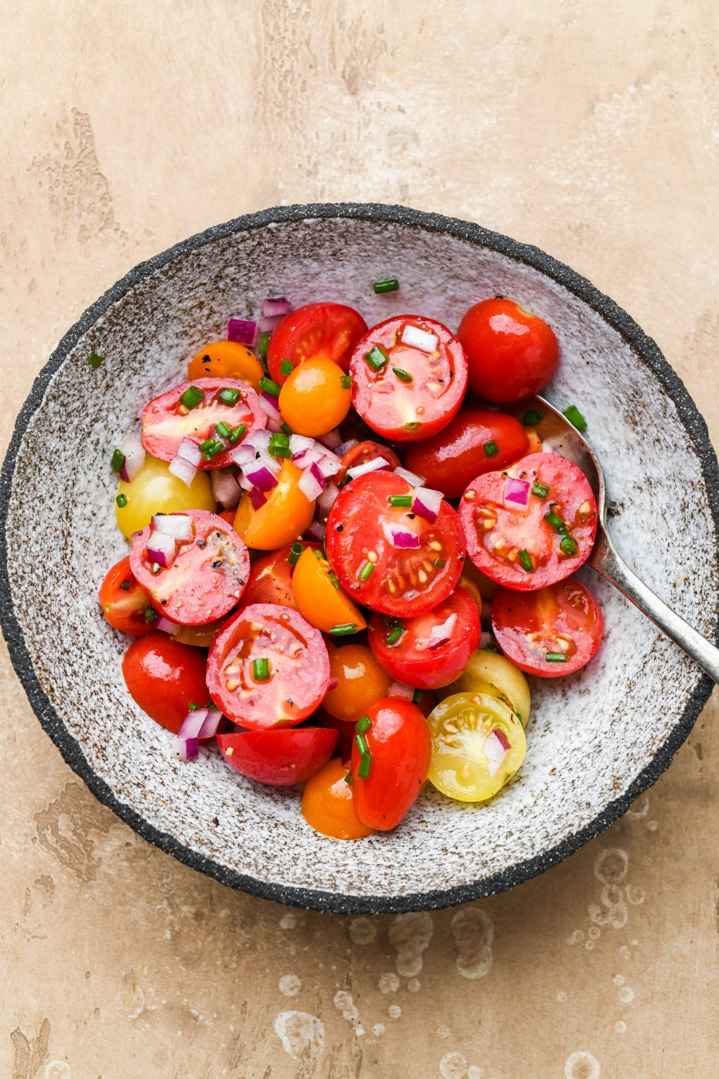 A small textured bowl with the ingredients for the cherry tomato salad garnish after mixing.