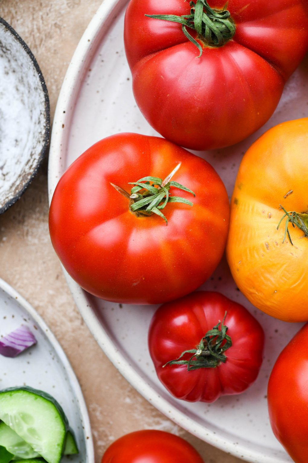 Close up shot of red and yellow heirloom tomatoes on a white textured plate.