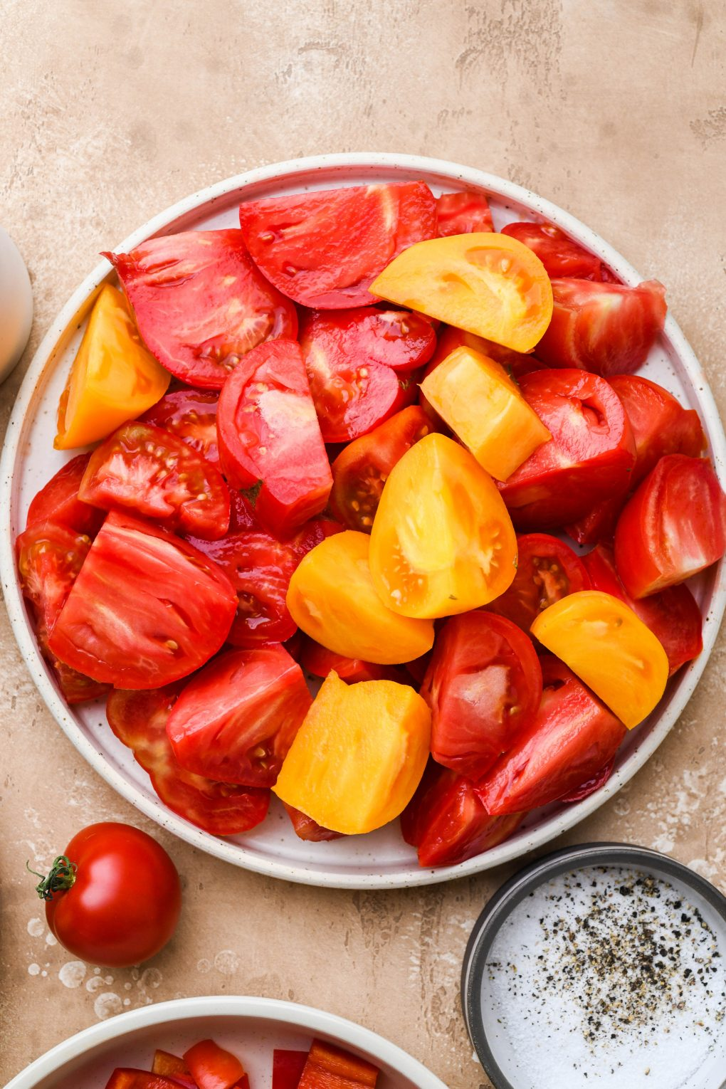 Overhead shot of a large speckled plate filled with red and yellow chopped heirloom tomatoes. On a light brown speckled background.