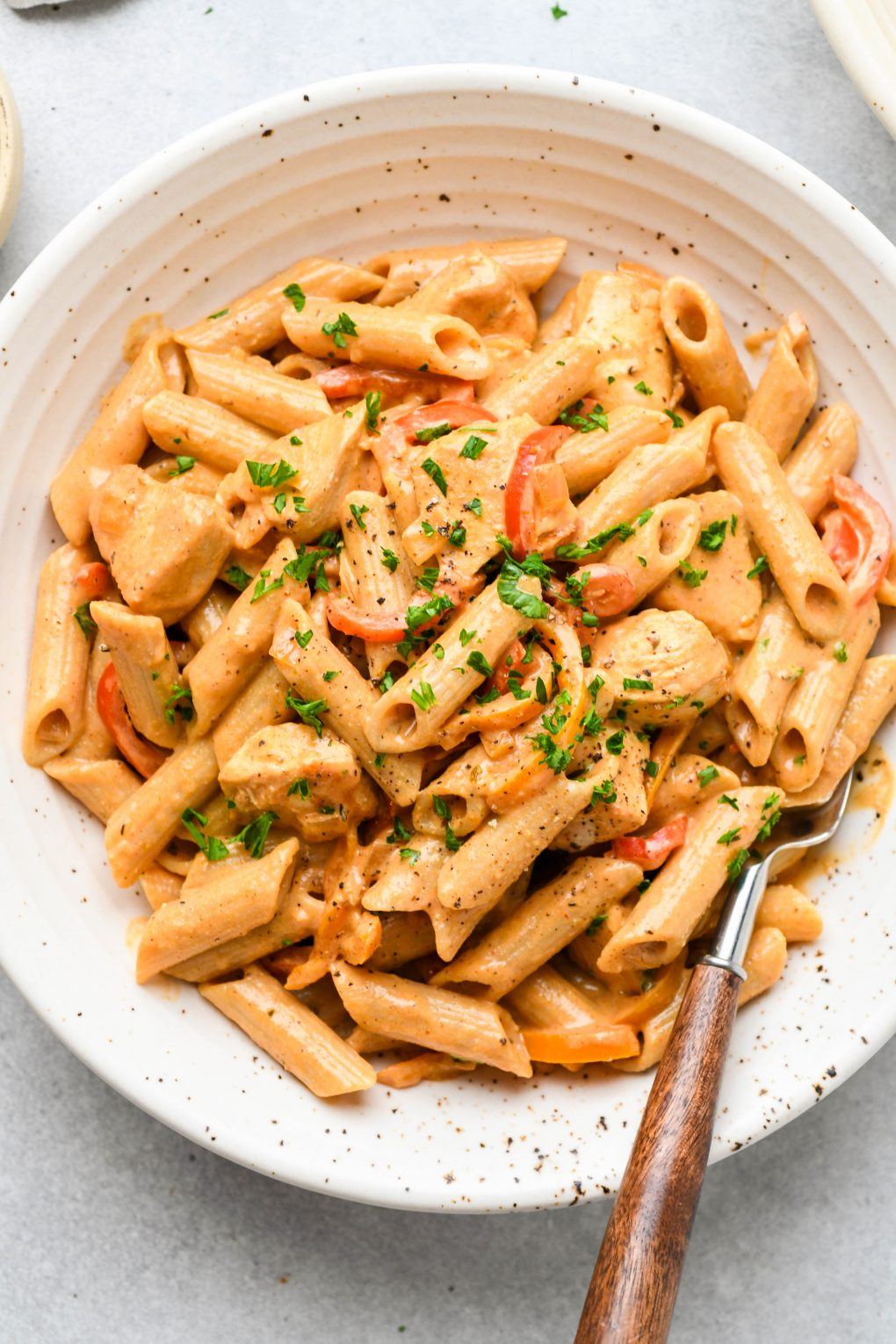 Large speckled shallow bowl filled with creamy cajun chicken penne pasta. Topped with a sprinkle of parsley and a wooden handled fork tucked into the side of the bowl.