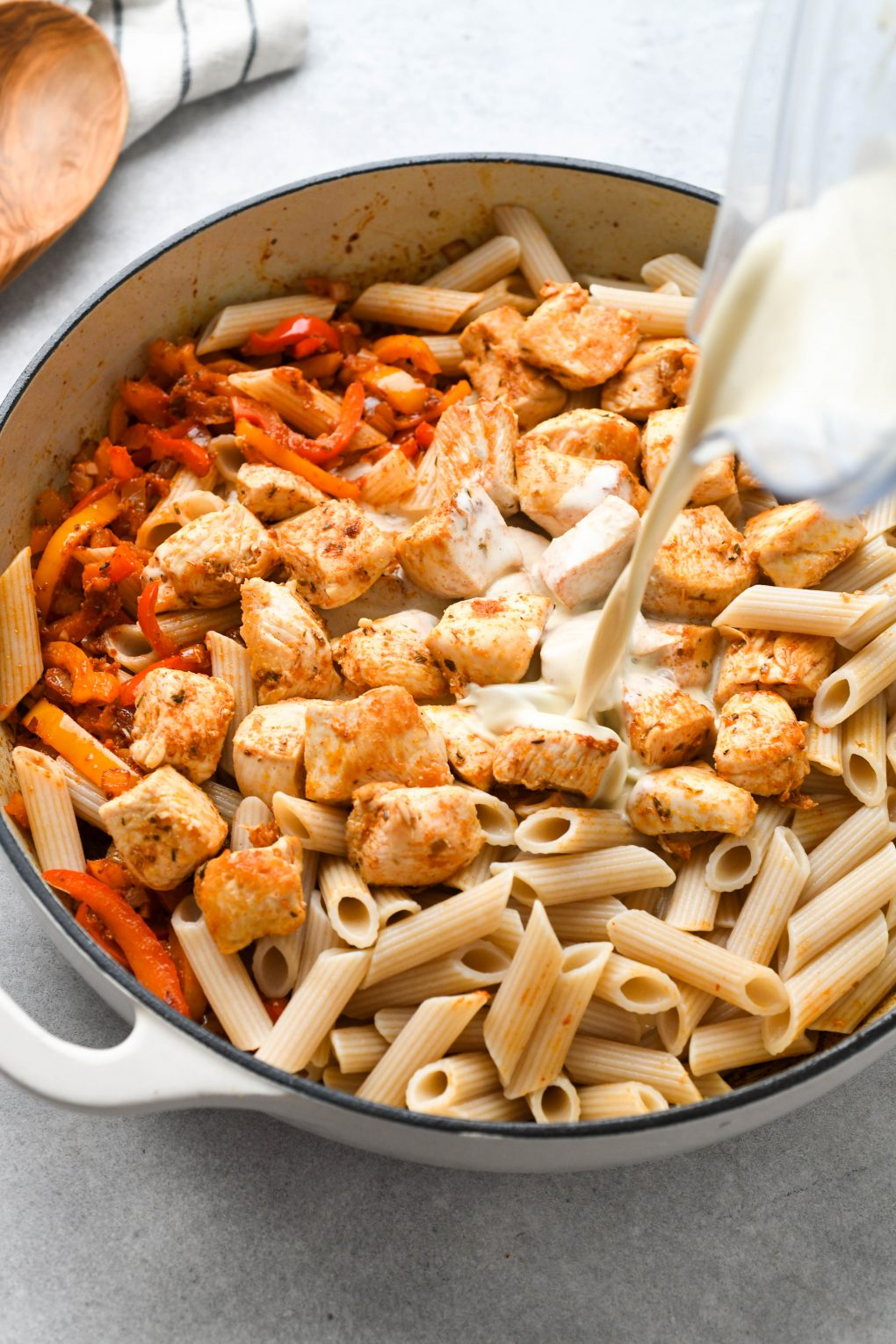 Cooked veggies, chicken, and pasta in a large white ceramic skillet with cashew cream sauce being poured in from a blender container.
