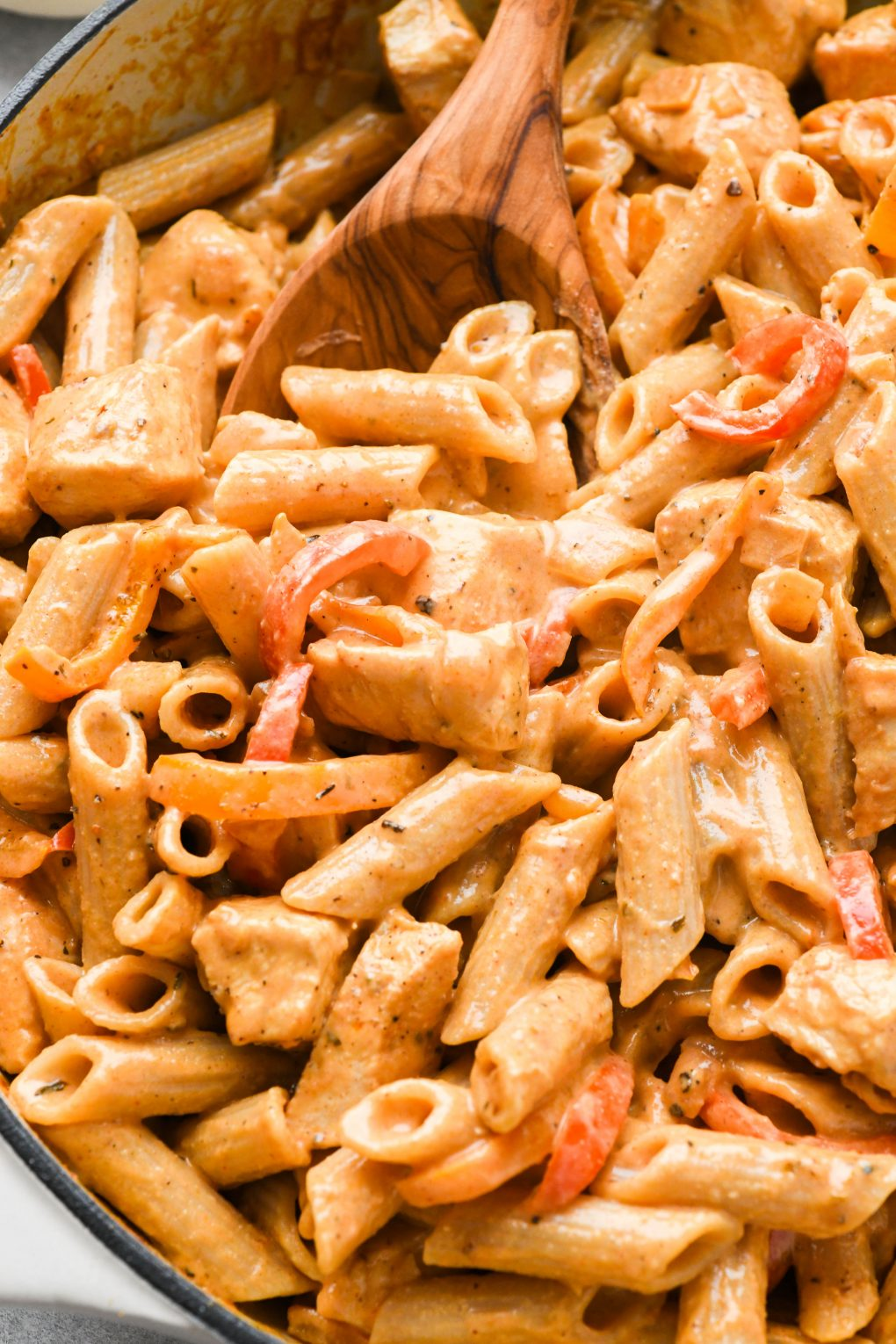 Close up shot of a spoon scooping creamy cajun chicken pasta out of a large ceramic skillet.