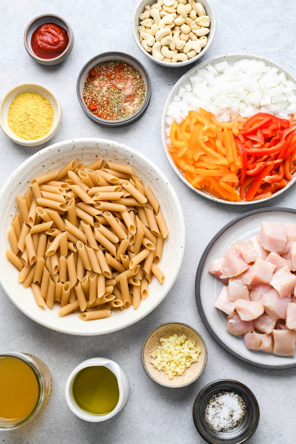 Ingredients for cajun chicken pasta on a light colored background. A bowl of cajun spice blend, a bowl of nutritional yeast, a bowl of chopped garlic, a bowl of uncooked penne pasta, a plate with chopped onion and bell peppers, and a plate with diced raw chicken.