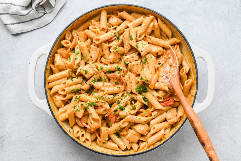 Large white ceramic skillet filled with creamy cajun chicken pasta, on a light colored background with a folded striped linen.