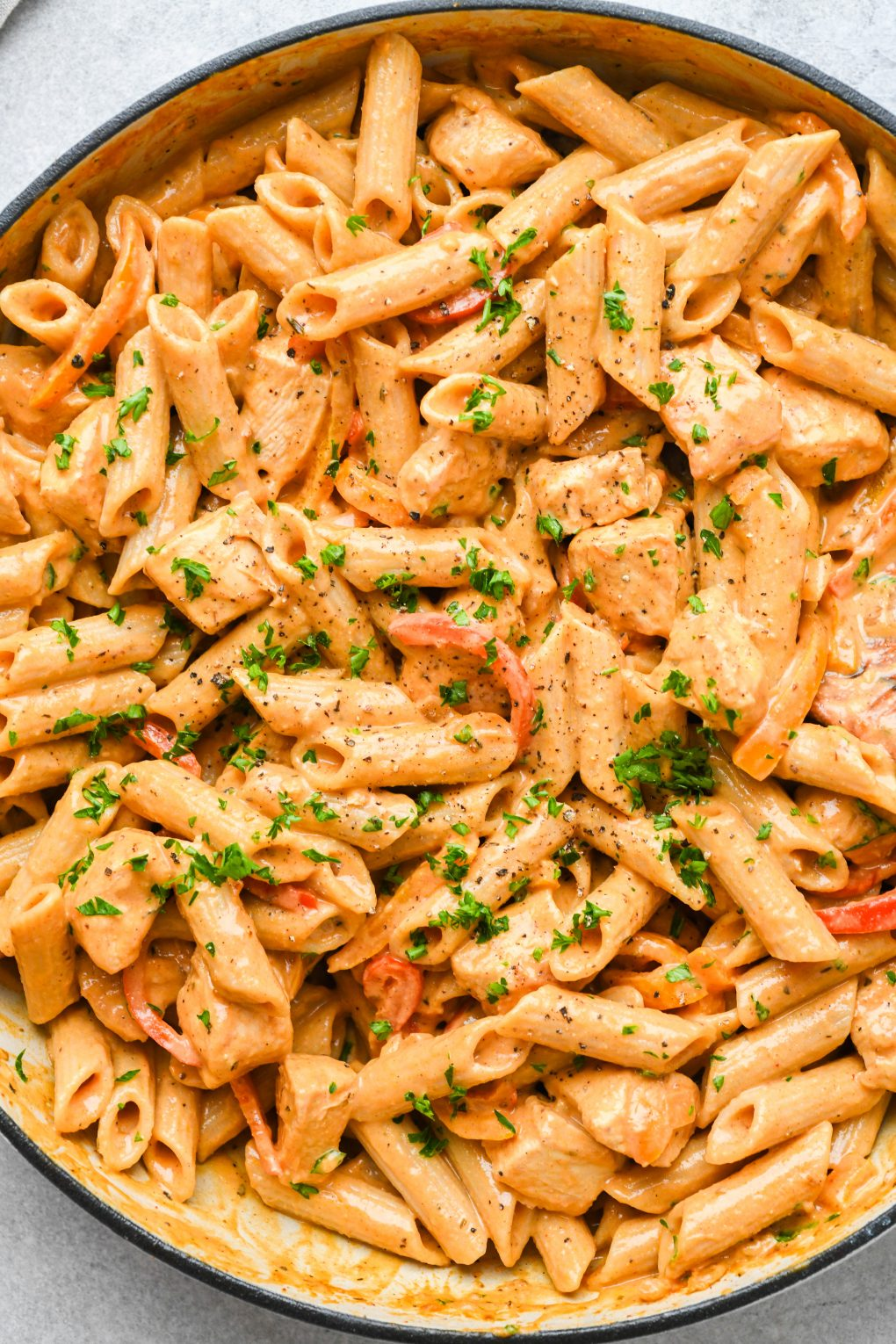 Close up image of a ceramic skillet filled with super creamy cajun chicken pasta. Topped with chopped parsley on a light colored background.