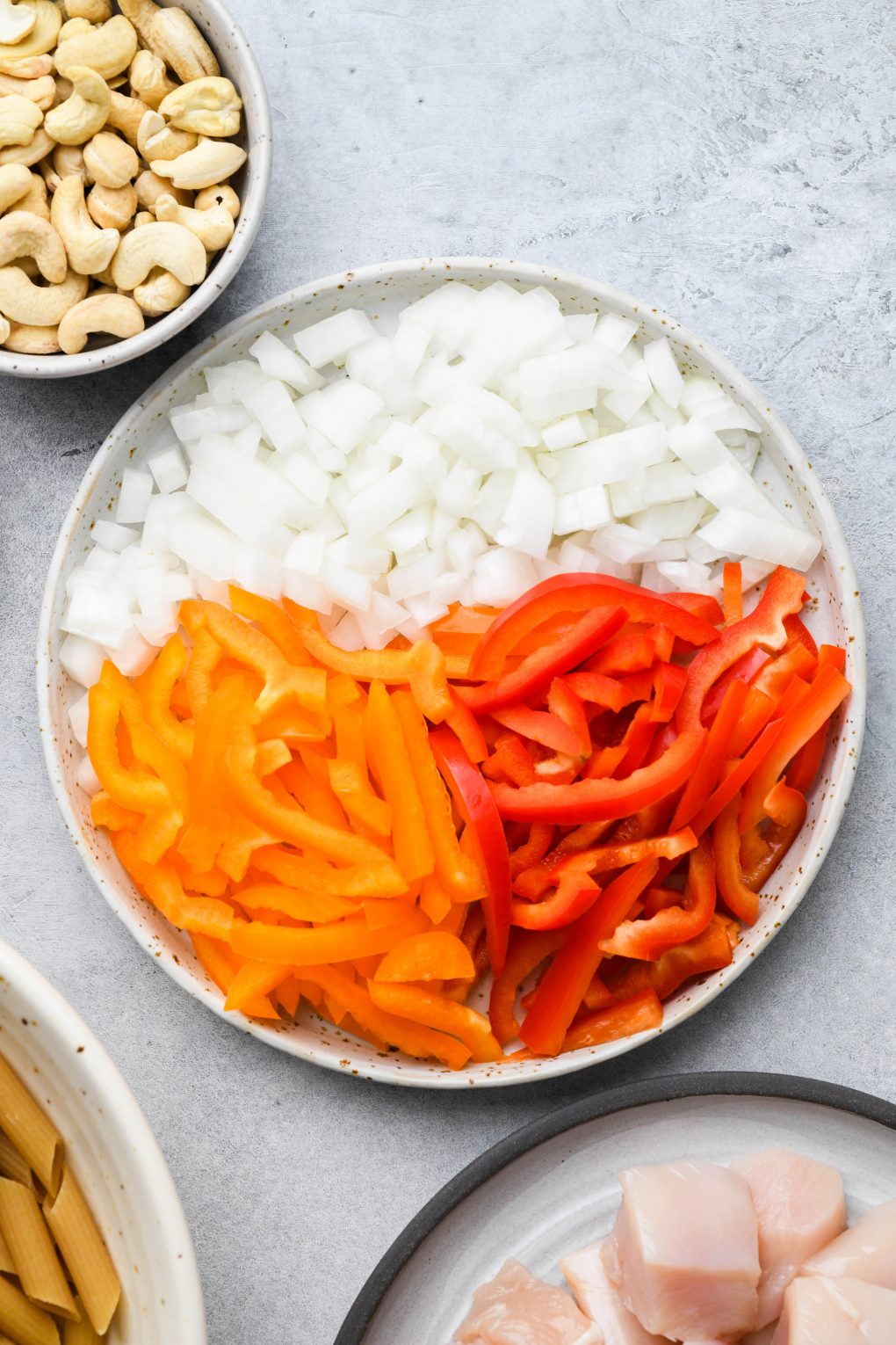 A large speckled white plate filled with chopped onion, orange pepper and red pepper on a light colored background.