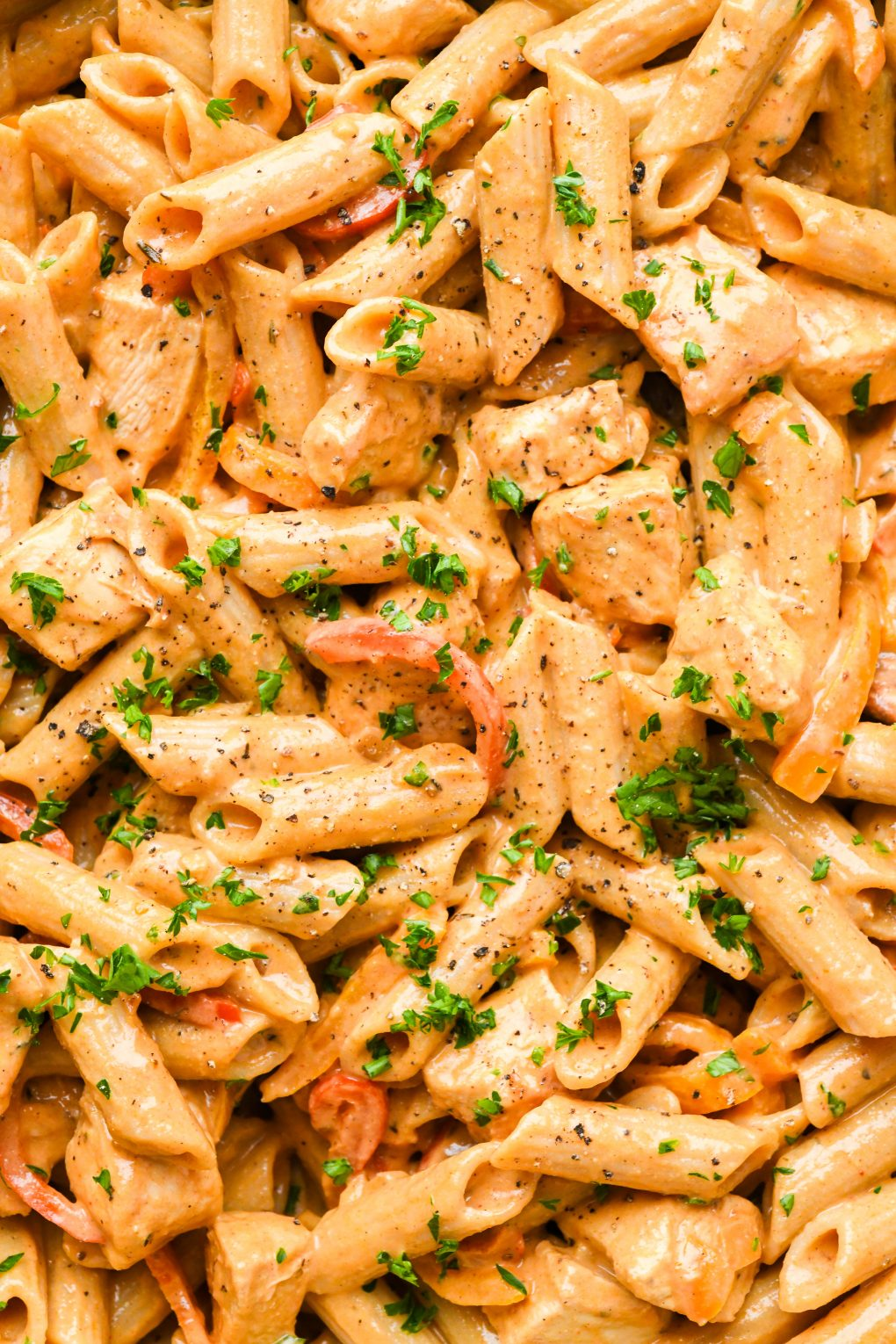 Close up macro style shot of creamy cajun chicken penne pasta topped with chopped parsley.